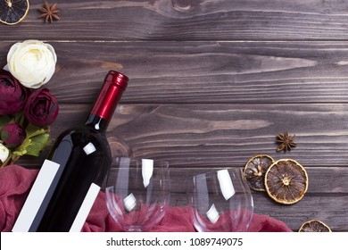 Wine bottle wineglass peonys on white wooden table.
