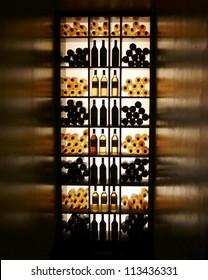 Wine bottles arranged on shelves with backlit