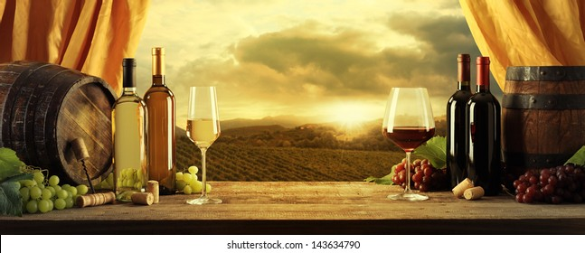 Wine bottles, barrels and vineyard in sunset
