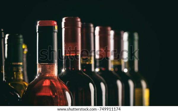 Коллекция бутылок вина на черном фоне, пространство для копирования