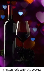 Wine bottles with glass and grapes on love heart Bokeh Background