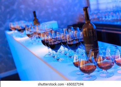 Wine bottles and glasses with alcohol drinks (wine, liquor, brandy) on a counter in a lounge night club lit with blue lights, shot at a party after a business conference
