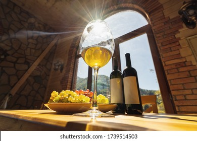 Wine bottles, grape and glasse of wine with sun rays on the wooden table with bavkground mountains in window. Selective focus.