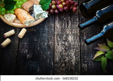 Wine bottles with grape leaves on wooden background with copy space, selective focus.