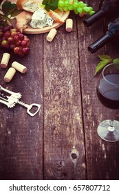 Wine bottles with grape leaves on wooden background with copy space.
