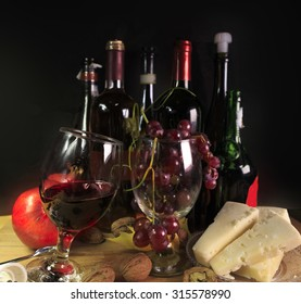 wine bottles grapes, chees pomegranate - black background
