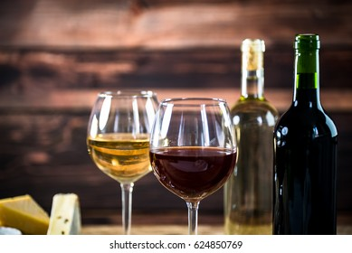 Wine bottles with grapes and cheese on wooden rustic background. copy space