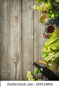 Wine bottles with grapes and corks on wooden background with copy space