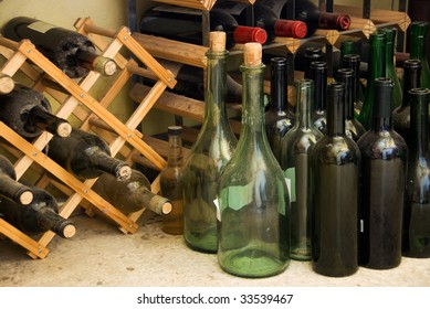 Wine bottles on floor and on wine rack