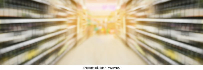 wine bottles on liquor shelves in supermarket with motion blur panorama view
