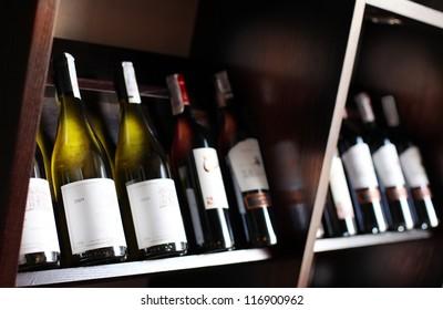Wine bottles on a wooden shelf. Wine cellar.