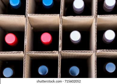 Wine bottles of red and white wine in cardboard box view from top on colourful caps. Full frame macro crop backgrounds. Horizontal orientation