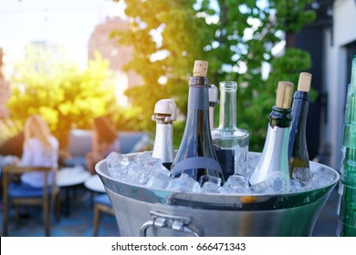 Wine bottles set in bucket, NYC rooftop