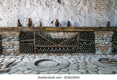 Wine bottles in a shelf in old wine cellar in Georgia with traditional kvevri in front where wine gets fermented