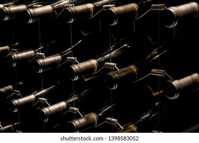 Wine bottles stored laying on their side on a wine rack.