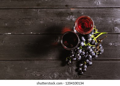 wine with branches of white grapes. On a wooden table.
