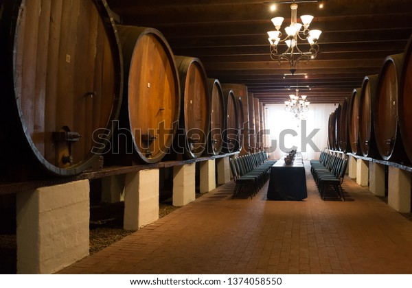 wine cellar with huge and massive wine vats or barrels containing wine and table and chairs laid out for wine tasting experience at a winery in the Cape Winelands, South Africa