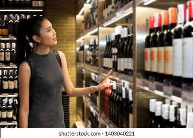 Wine Cellar Shop with many bottles brand on shelf and pick up select by Asian black hair adult working woman, in temperature control room to keep winecellar fresh long time, concept decision making