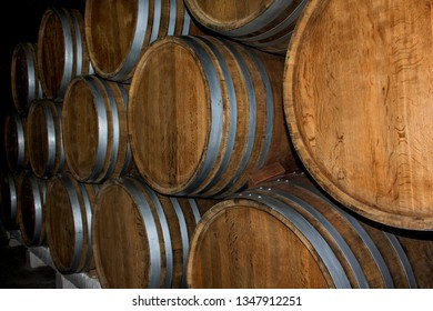 Wine cellar with stacked oak old barrels for maturing wine