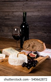 wine and cheese background still life on a wooden table with grape and bread