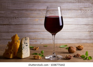 Wine and cheese. Wine glass with cheese, nuts and basil on wooden background. Wine and food concept