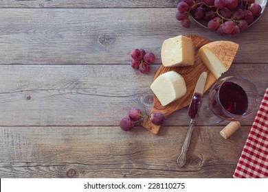 Wine, cheese and grapes on wooden table. View from above with copy space