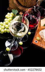 Wine and cheese on black  table with fresh grapes