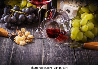Wine and cheese on a dark wooden background