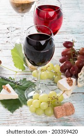 Wine and cheese on wooden table with fresh grapes