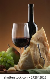 Wine and cheese/ red wine glass/ red wine bottle/wine grapes/ cheese plate