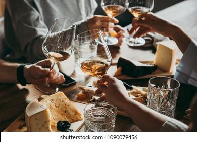 Vinho e queijo servidos para uma festa amigável em um bar ou restaurante.