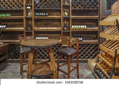 wine chiller cabinet in wine cellar in restaurant, wine room interior, hardwood furniture, oak table and oak bar stool