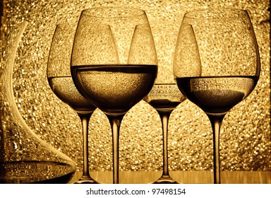 Wine container with four glasses of white wine