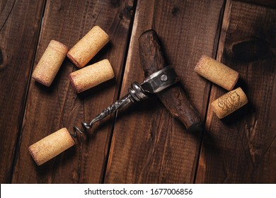 Wine corks and corkscrew on a wooden background