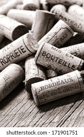 Wine corks from opened bottles with generic French winemaker wording naming local bottling at the castle or at the property in a loose pile on an old weathered vineyard cellar wood table in France