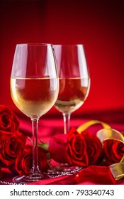 Wine cups red roses and romantic setting for two in red.
