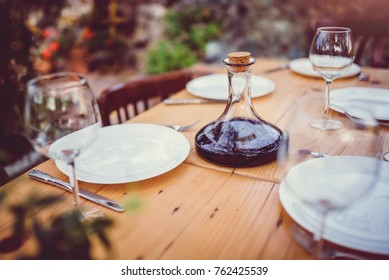 Wine decanter and glasses on dining table in backyard patio