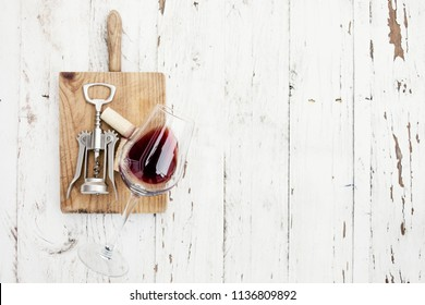 Wine degustation concept -  red  wine  glass, wine corks  and corkscrew on white wooden table with copespace