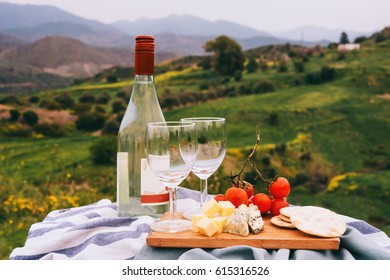 Wine and different appetizers at a picnic in the mountains