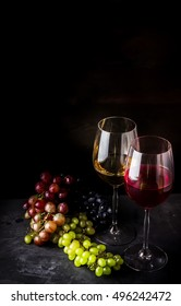Wine and different types of grape on dark background. Place for text.