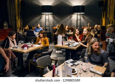 Wine dinner at the restaurant with oysters and seafood. People eat Oysters and risotto gourmet cuisine. Mussels for dinner, visitors first try oysters. Russia, Sverdlovsk, 19 October 2018