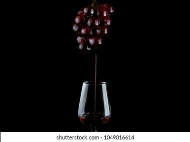 Wine draining off grapes and into wine glass.