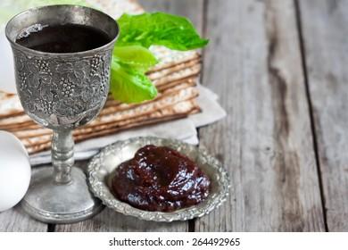Wine, egg, bitter salad leaves, matzot and haroset - traditional jewish passover celebration elements. Copy space background.