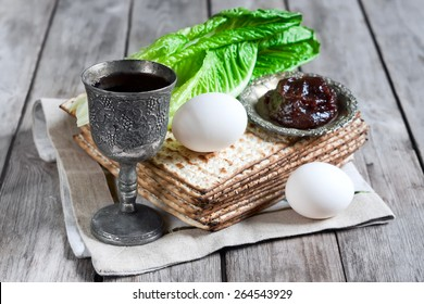 Wine, egg, bitter salad leaves, matzot and haroset - traditional jewish passover celebration elements. Selective focus.