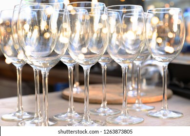Wine empty transperent glasses in row on bar table with blurred lights background. Festive concept