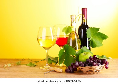 Wine and fruits on yellow background