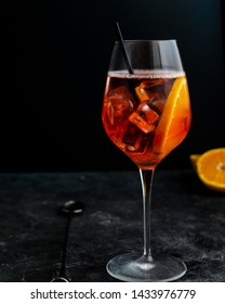 Wine glass with aperol spritz, italian alcoholic cocktail on dark background