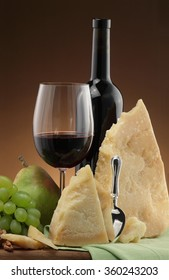 Wine glass / wine bottle/ cheese/ parmesan / nuts / fruits/ wine and cheese