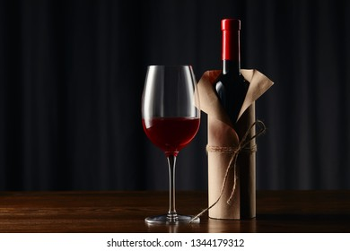 Wine glass and bottle in paper wrapper on wooden surface