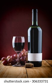 Wine Glass with bottle of red wine and cluster of grape on wooden table